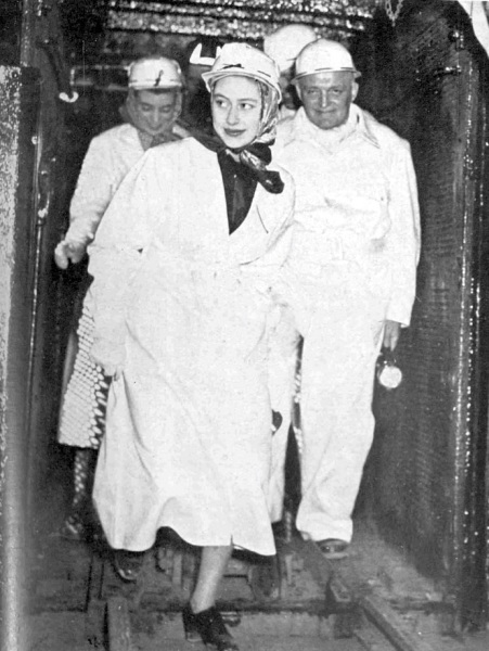 The Princess is seen coming out of the pit cage after spending an hour down the mine; with her are Mr Alan Hill, the area general manager, and Miss Iris Peake, her Lady-in-Waiting.